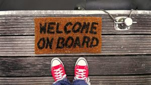 A person is standing in front of a doormat saying 'welcome on board'.