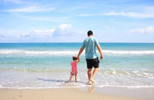 There is a father with his daughter at the beach in Louisiana.